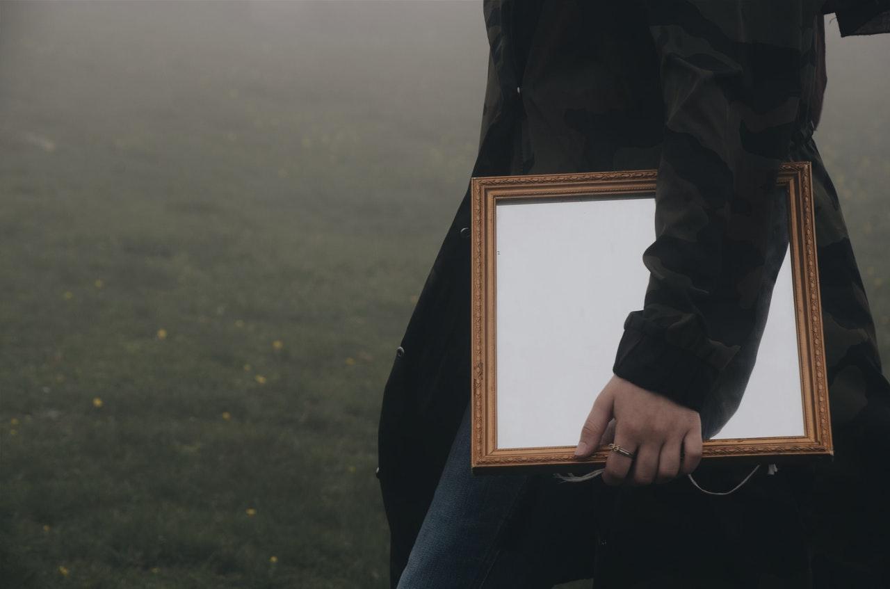 man holding brown framed mirror