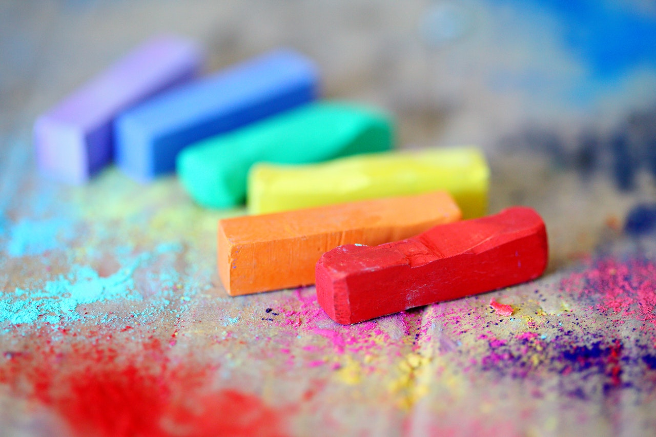assorted colored chalks on wooden surface