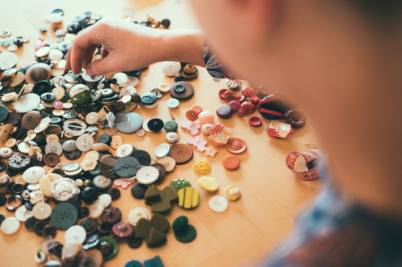men sorting buttons on table