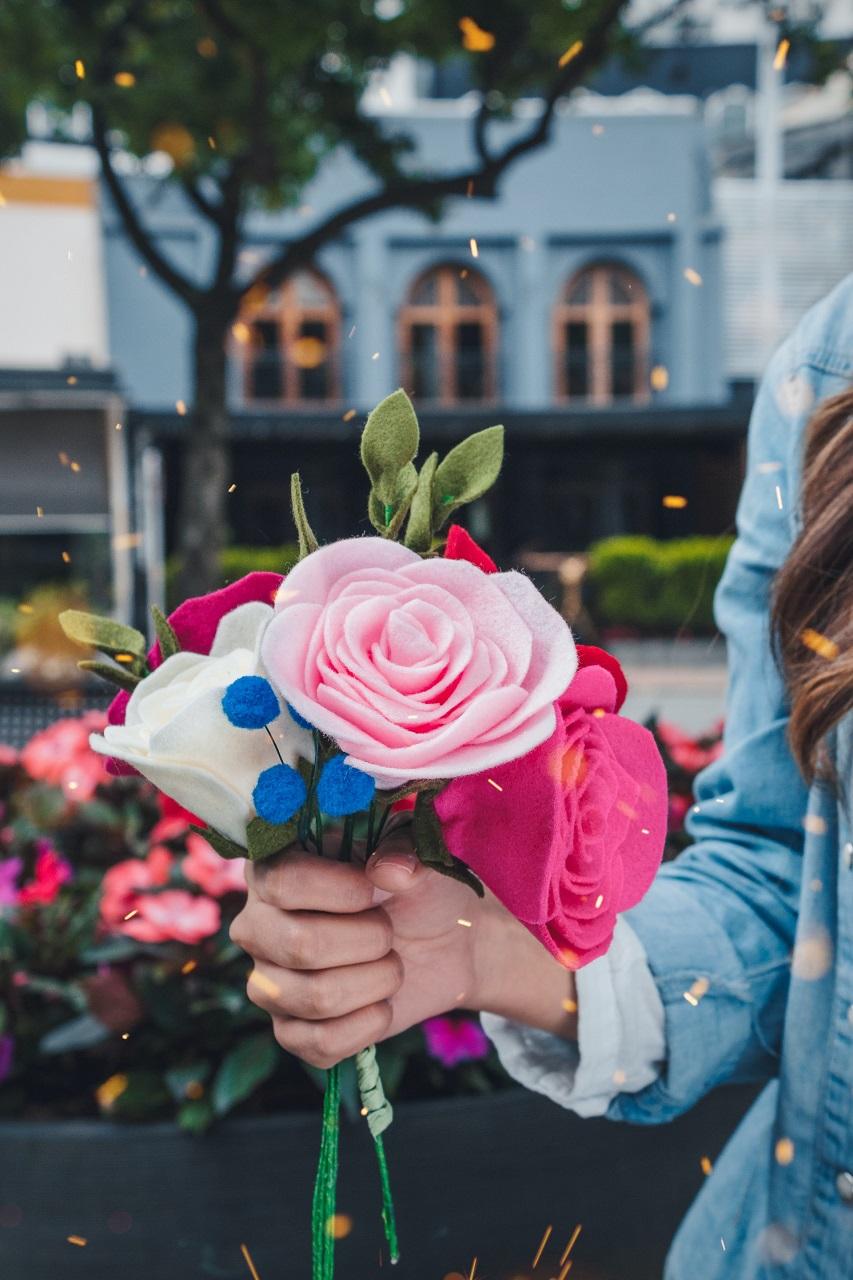 women holding petaled faux flowers